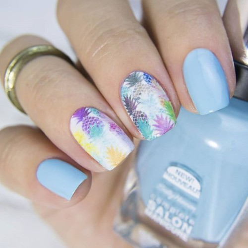 blue and white nails with colorful pineapples