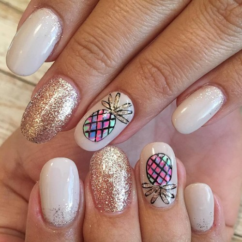 colorful pineapples on nails with glitter leaves