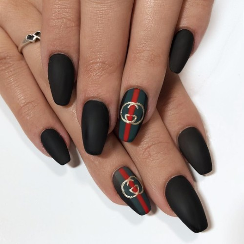 black Gucci nails with Gucci label and stripes