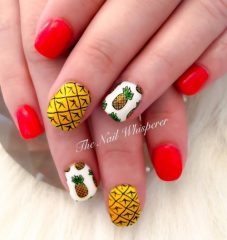red nail design with pineapples