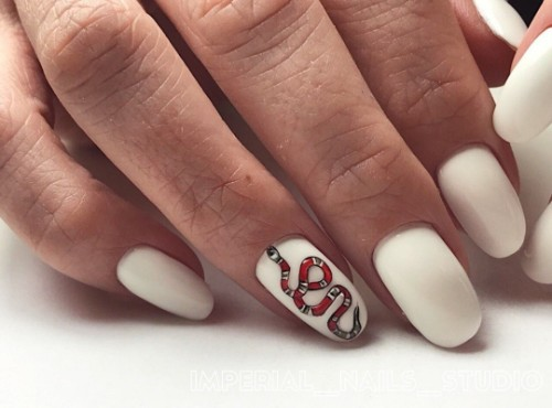 white Gucci nails with a snake