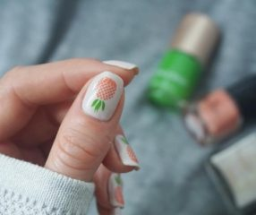 white nails with orange pineapples