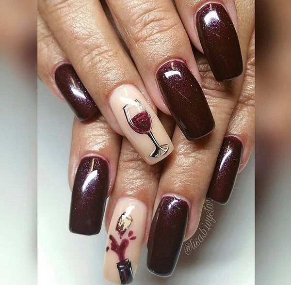 long dark red nails with a glass of wine