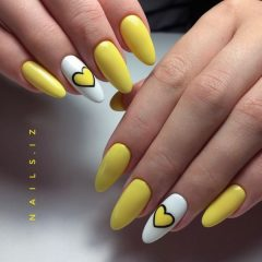 oval almond shaped manicure with white accent nails and yellow hearts