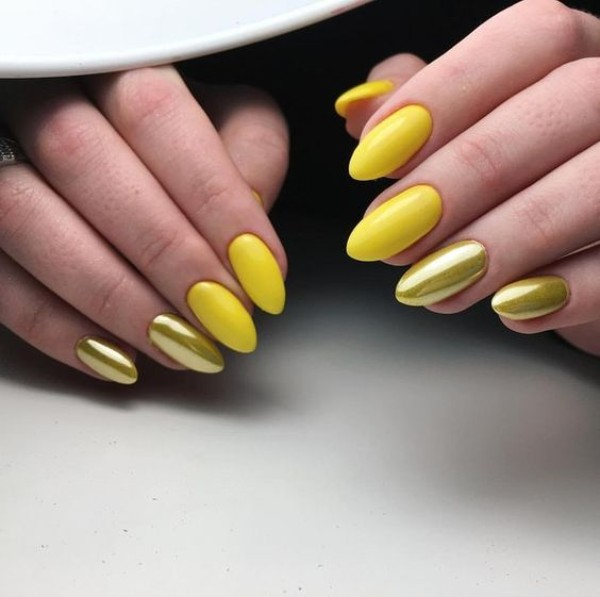 almond yellow mani with several nails covered with pearlish finish