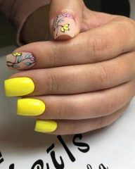 bright yellow manicure with two accent matte nails and colorful leaves and flowers