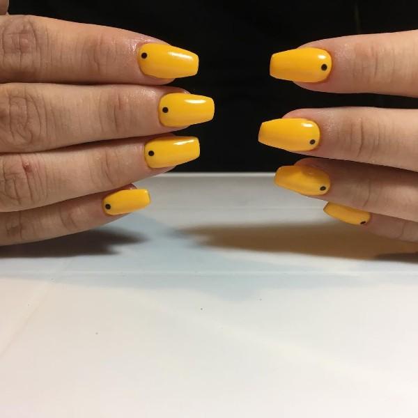 minimalistic yellow nail design with dots