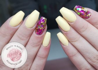 light yellow manicure with pink accent glitter nails